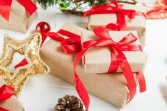 Composição dos feriados do Natal com os presentes no papel do ofício com a fita vermelha do cetim no fundo de madeira branco com  Imagens de Stock Royalty Free