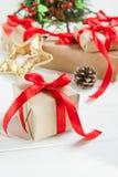 Composição dos feriados do Natal com os presentes no papel do ofício com a fita vermelha do cetim no fundo de madeira branco com  Imagem de Stock Royalty Free