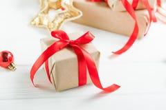 Composição dos feriados do Natal com os presentes no papel do ofício com a fita vermelha do cetim no fundo de madeira branco com  Foto de Stock Royalty Free