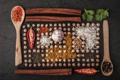 Composição dos grãos-de-bico e da especiaria com os utensílios de mesa de madeira horizontais Foto de Stock Royalty Free