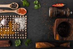 Composição dos grãos-de-bico e da especiaria com utensílios de mesa de madeira na tabela escura Fotos de Stock