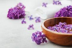 A composição dos termas e do bem-estar com lilás perfumado floresce a água na bacia e na toalha de terry de madeira no fundo de p Fotografia de Stock