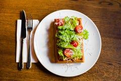 A composição dos waffles belgas com salat, tomates, queijo e vegetais do othe colocados na tabela de madeira Imagens de Stock