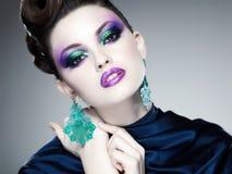 Composição e penteado azuis profissionais na cara bonita da mulher imagem de stock royalty free