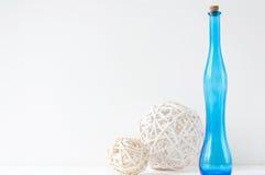 Composição elegante mínima com bolas do rattan e a garrafa azul Fotografia de Stock