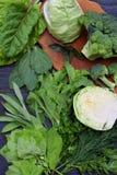 Composição em um fundo escuro dos legumes verdes que contêm o ácido fólico, riboflavina, vitamina B9, B2, K, C - couve, broc Fotos de Stock Royalty Free