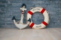 Composição em um tema do mar com uma âncora e um anel de vida em uma parede de tijolo cinzenta Fotos de Stock Royalty Free