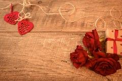 A composição em uma tabela de madeira com rosas vermelhas, presente, fez crochê corações, e fitas Conceito do dia do ` s do Valen Fotos de Stock