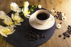 Composição feita do copo do chá preto com um fundo preto e marrom Copo do café preto com flor branca Foto de Stock Royalty Free