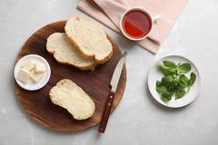 Composição lisa da configuração com pão, manteiga e copo do chá imagem de stock