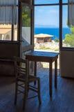 Composição romântica de Grécia: tabela e cadeira perto da janela e do mar azul profundo atrás Imagens de Stock Royalty Free
