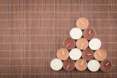 Composição triangular de velas da luz do chá em um placemat de bambu imagens de stock royalty free