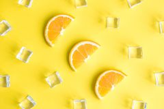 A composição tropical do fundo da vista superior fez de fatias alaranjadas do fruto e dos cubos de gelo abstratos no amarelo fotografia de stock