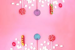 Composi??o colocada lisa com quadro dos pirulitos e dos marshmallows e espa?o para o texto no fundo cor-de-rosa imagens de stock royalty free