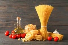Composi??o com massa, azeite, tomates e alho na tabela de madeira imagem de stock