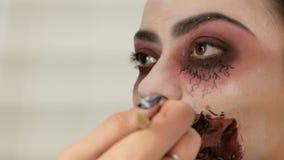Composi??o de Dia das Bruxas Uma imagem de uma senhora assustador com uma boca ensanguentado A mão do maquilhador escova os bordo filme