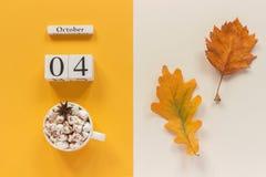 Composi??o do outono Calend?rio o 4 de outubro de madeira, copo do cacau com marshmallows e folhas de outono amarelas no fundo be fotografia de stock