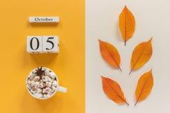 Composi??o do outono Calend?rio o 5 de outubro de madeira, copo do cacau com marshmallows e folhas de outono amarelas no fundo be imagens de stock