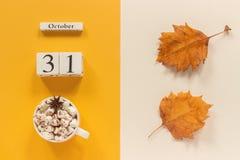 Composi??o do outono Calend?rio o 31 de outubro de madeira, copo do cacau com marshmallows e folhas de outono amarelas no fundo b fotografia de stock