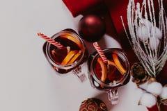 Composición adornada de tazas con el vino reflexionado sobre en bufanda hecha punto, cierre para arriba foto de archivo