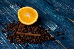 Composición aromática de los granos de las naranjas, del canela y de café en un fondo azul marino Visión superior Imagen de archivo