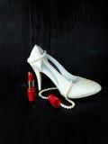 Composición atractiva hecha de los talones blancos, del lápiz labial rojo y del collar de la perla Foto de archivo libre de regalías