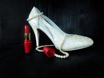 Composición atractiva hecha de los talones blancos, del lápiz labial rojo y del collar de la perla Fotos de archivo libres de regalías