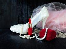 Composición atractiva hecha de los talones blancos, del lápiz labial rojo y del vestido rosado Imágenes de archivo libres de regalías