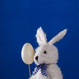 Composición con el conejo del peluche y el huevo de Pascua serios Fotos de archivo