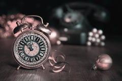 Composición con el despertador del vintage que muestra cinco a la medianoche Fotografía de archivo