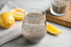 Composición con el vaso de agua, las semillas del chia y el limón foto de archivo libre de regalías