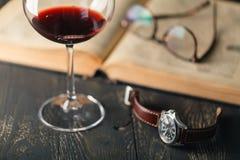 Composición con el vidrio de vino con los libros viejos en cierre de la tabla para arriba Fotografía de archivo libre de regalías
