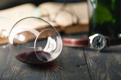 Composición con el vidrio de vino con los libros viejos en cierre de la tabla para arriba Imagenes de archivo