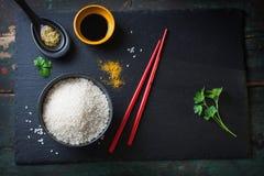 Composición con la comida asiática - arroz para el sushi, las especias, las salsas y los palillos Foto de archivo