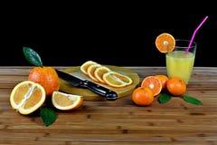 Composición con la fruta cítrica y el vidrio cortados de zumo de naranja imagenes de archivo