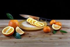 Composición con la naranja cortada en la tabla de madera fotos de archivo