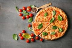 Composición con la pizza, el aceite, los tomates de cereza y la albahaca fresca Fotografía de archivo libre de regalías