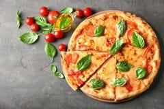 Composición con la pizza, los tomates de cereza del aceite y la albahaca fresca Fotografía de archivo