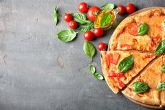 Composición con la pizza, los tomates de cereza del aceite y la albahaca fresca Foto de archivo libre de regalías
