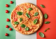 Composición con la pizza, los tomates de cereza y la albahaca fresca Imagen de archivo libre de regalías