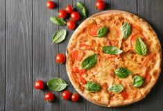 Composición con la pizza, los tomates de cereza y la albahaca fresca Foto de archivo libre de regalías