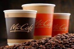 Composición con la taza y las habas de café de McCafe Fotografía de archivo