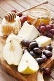 Composición con la uva, el queso y la miel Fotos de archivo