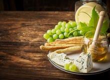 Composición con la uva, el queso y la miel Imagen de archivo libre de regalías