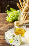 Composición con la uva, el queso y la miel Imágenes de archivo libres de regalías