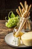 Composición con la uva, el queso y la miel Foto de archivo libre de regalías