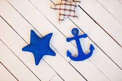 Composición con las estrellas de mar y el ancla de la materia textil Imagenes de archivo