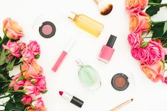 Composición con las flores color de rosa, los brotes, las hojas del verde y los cosméticos femeninos en el fondo blanco Endecha p Foto de archivo