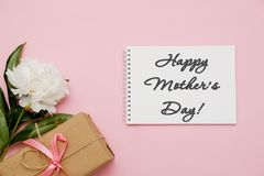 Composición con las flores, el regalo y el cuaderno en fondo rosado Día de madres feliz de la tarjeta de felicitación Endecha pla fotografía de archivo