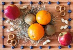 Composición con las manzanas rojas, los kiwis y las frutas anaranjadas Foto de archivo